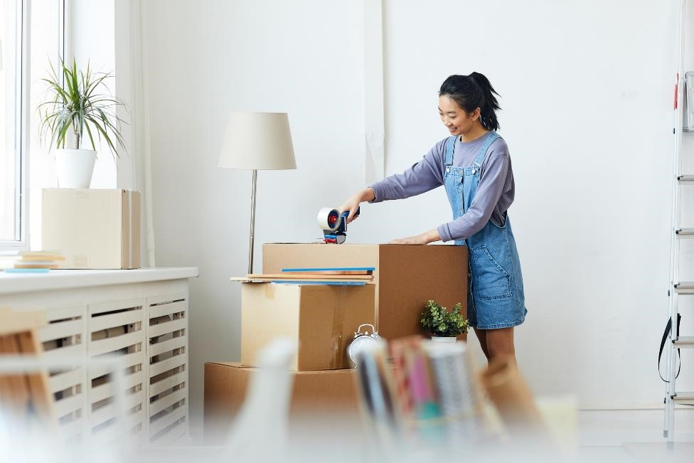 Woman taping a storage box closed.