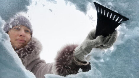 Woman using snow scraper to remove snow and ice from windshield.