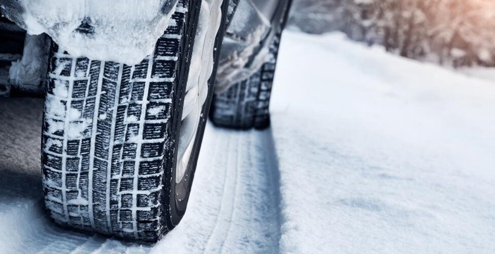 Car with snow tires leaving snow tracks.
